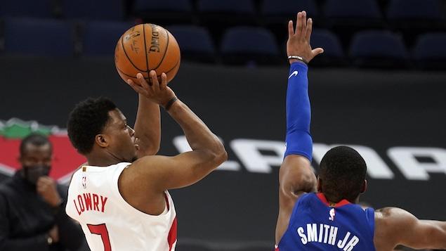 Le numéro 7 des Raptors s'apprête à tirer tandis qu'un adversaire plonge pour le bloquer.