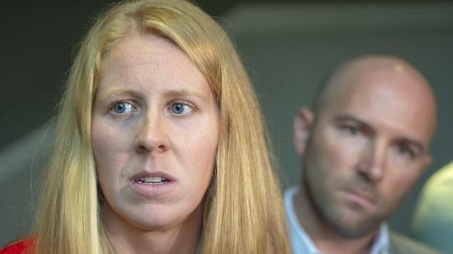 Gros plan du visage d'une femme qui répond à des questions devant des micros.