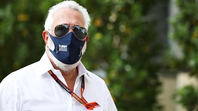 Muni d'un masque, en chemise blanche et avec des lunettes de soleil miroir, il regarde le photographe.