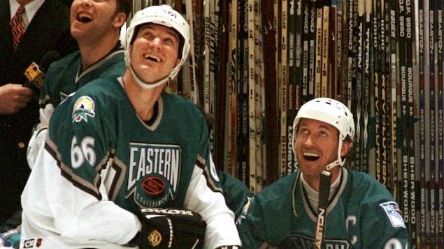 Deux joueurs au banc sourient.