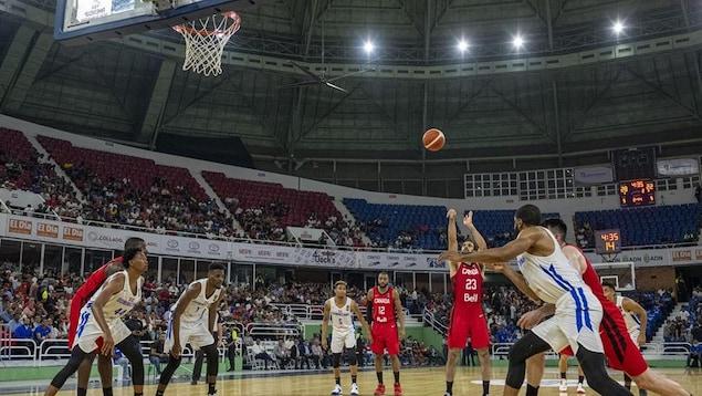 Des joueurs sont sur un terrain de basketball.