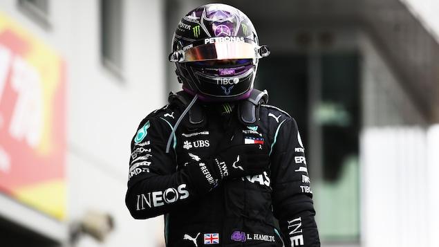 Le Britannique Lewis Hamilton, casqué, se frappe la poitrine du poing.