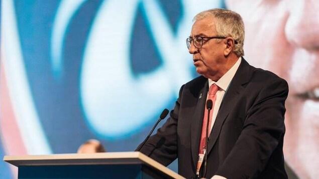 Un homme derrière un lutrin prononce un discours.