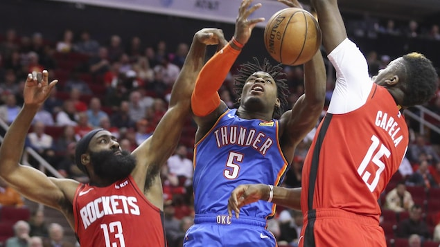 Il tente un lancer contré par deux joueurs des Rockets.