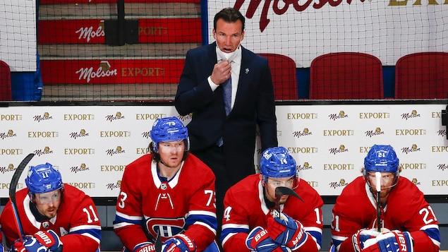 Vêtu d'un complet, debout derrière le banc du Canadien, l'entraîneur retient son masque sous son menton pour donner des instructions aux joueurs sur la glace.