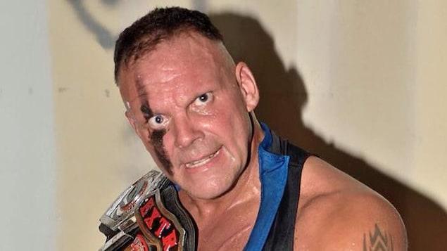Pierre-Carl Ouellet prend la pose avec une ceinture de championnat de lutte professionnelle.