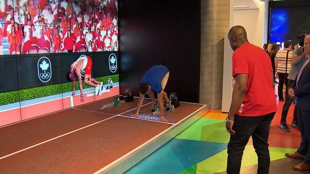 Bruny Surin prodigue des conseils à un utilisateur du simulateur de sprint.