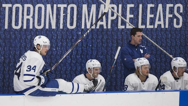 Un joueur de hockey est assis sur la bande alors que ses coéquipiers assis au banc suivent l'action des yeux.