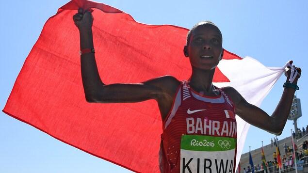 Elle porte le drapeau de Bahreïn au-dessus de ses épaules.