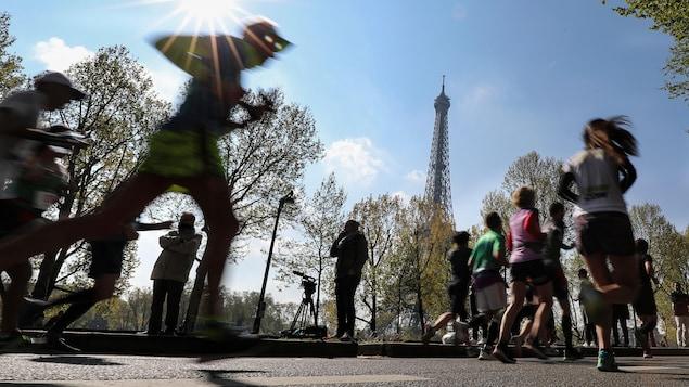 Les athlètes courent dans les rues de la capitale pendant le marathon de Paris, par beau temps.