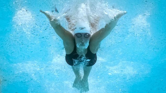 Un plan sous l'eau de la nageuse pendant son battement de papillon