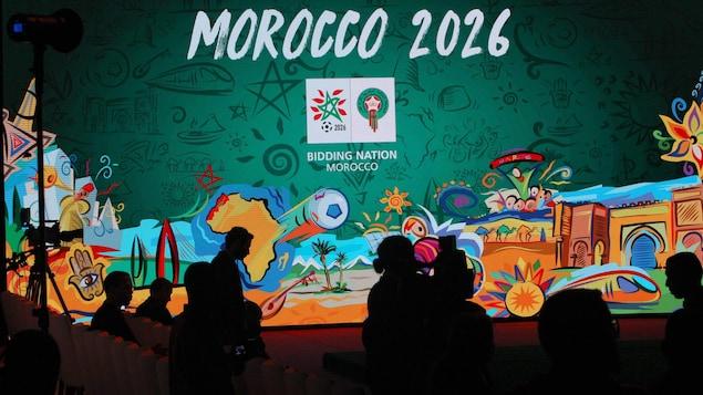 Écran présentant une image aux couleurs de la candidature du Maroc 2026.