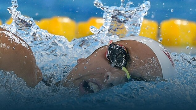 Une nageuse prend une respiration entre deux coups de bras.