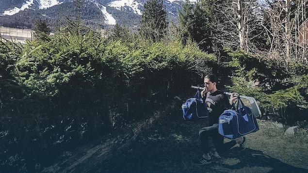 Mathieu Ayotte soulève deux sacs réunis par un bâton de hockey.