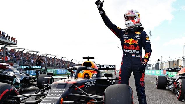 Max Verstappen salue la foule en levant la main droite.