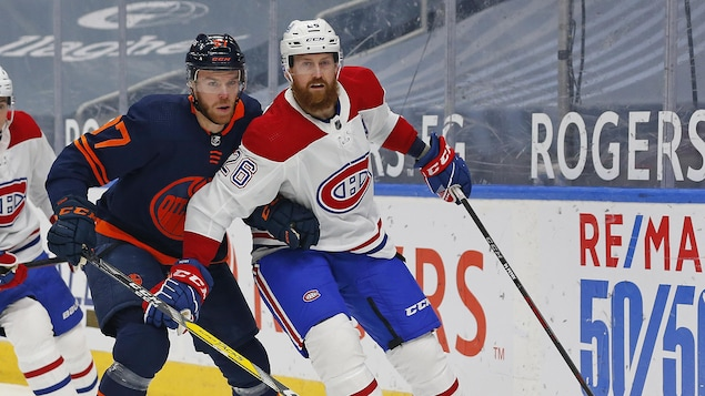 Jeff Petry tente de contenir McDavid derrière le filet.