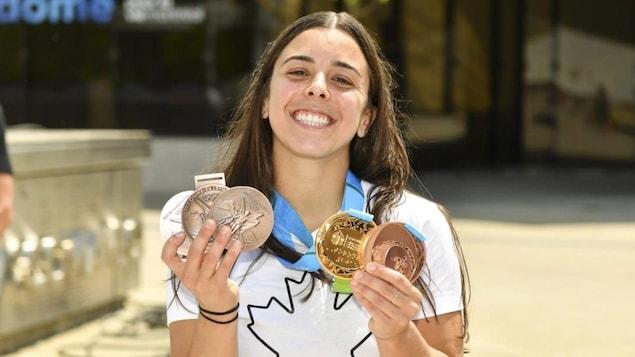 Une femme en blanc sourit avec des médailles au cou.