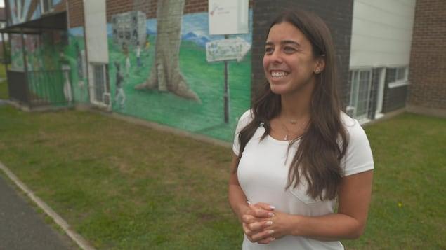 Meaghan Benfeito sourit devant un mur de brique.