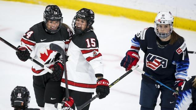 Deux joueuses de hockey célèbrent un but.