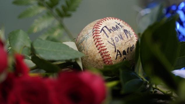 Balle de baseball déposée parmi des roses pour honorer Hank Aaron.