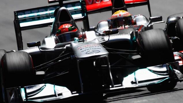 Michael Schumacher roule sur un circuit devant Lewis Hamilton en 2012.