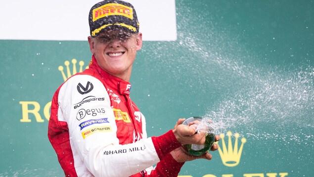Il arrose la foule avec du champagne.