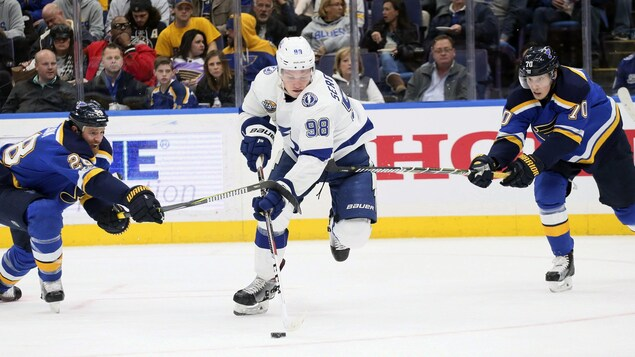 Mikhail Sergachev contrôle la rondelle en évitant deux joueurs des Blues de St-Louis.