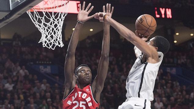 Le centre des Raptors de Toronto Chris Boucher bloque le tir du garde de Spencer Dinwiddie.