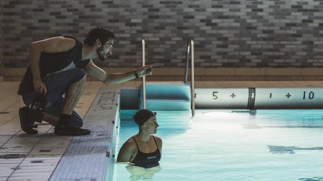 Il pointe vers le bout d'une piscine dans laquelle elle est visible à mi-buste.