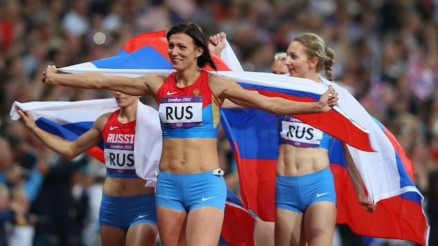 Des athlètes russes brandissent leur drapeau national après une course.