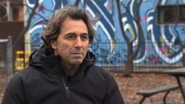 Il donne en entrevue dans un parc.