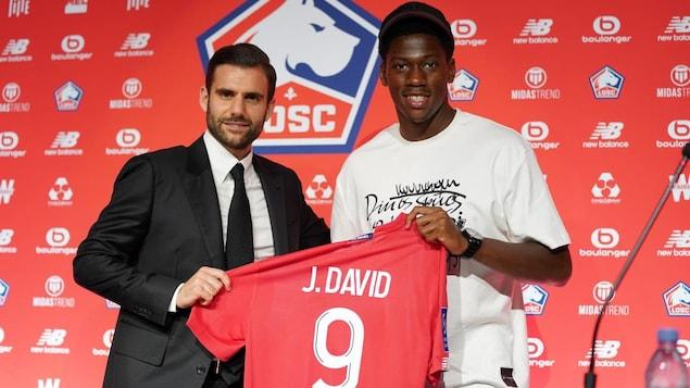 Un homme en complet tient un chandail de soccer rouge avec le joueur qui le portera avec sa nouvelle équipe.