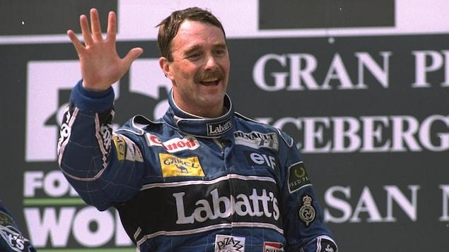 Un pilote de formule 1 salue la foule.