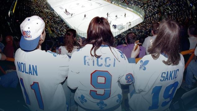 Trois partisans portant un chandail des Nordiques regardent le match au haut des gradins.