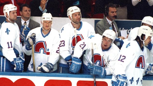 Des joueurs se tiennent debout du banc des Nordiques.