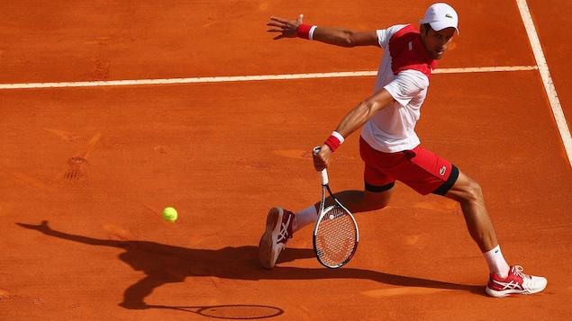 Novak Djokovic effectue un revers lors de son premier match sur la terre battue à Monaco