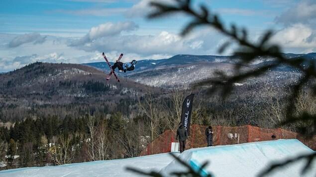 Olivia Asselin dans les airs après un saut, les skis croisées, des montagnes enneigées derrière elle.