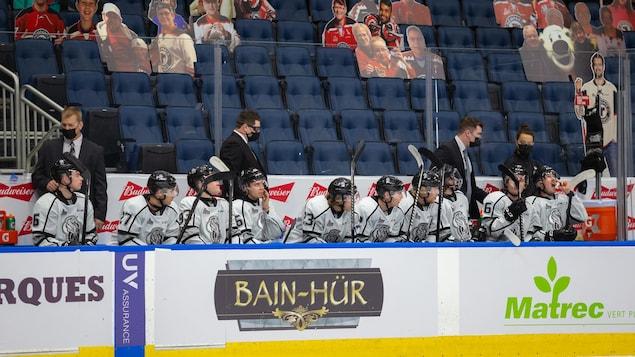 Des joueurs de hockey regardent un match de leur banc.