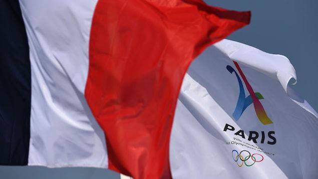 Le drapeau français flotte devant celui de  Paris 2024.