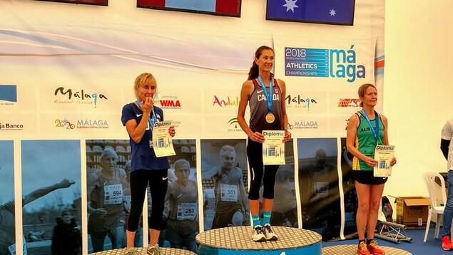 Le podium de la course de 800 m, catégorie 60-64 ans, aux Mondiaux d'athlétisme des maîtres. Au centre, médaillée d'or, Patty Blanchard; à gauche, Lesley Hinz (argent); à droite, Deborah Drennan. Chacune a son certificat souvenir de la course.
