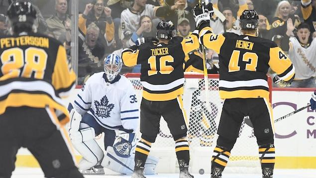 La foule crie à l'unisson après un but des Penguins alors que le gardien des Maple Leafs a l'air découragé.