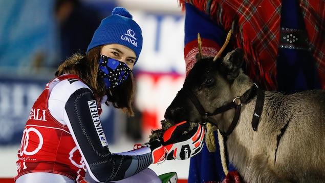La skieuse est agenouillée et caresse un renne.