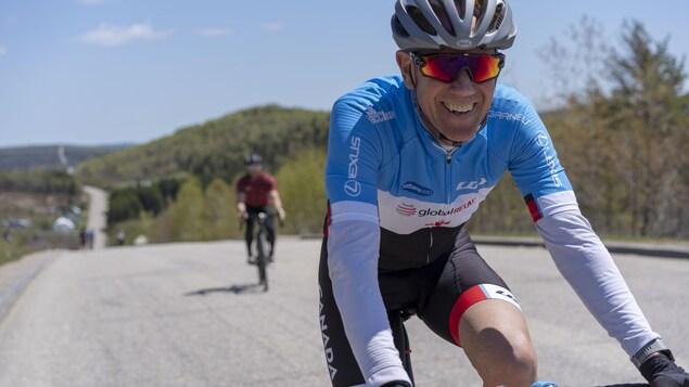 Il sourit à la caméra, sur son vélo.