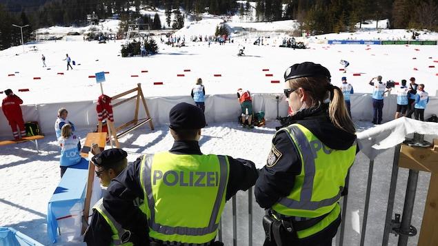Ils  surveillent l'action dans la zone d'arrivée aux mondiaux de ski de fond à Seefeld.