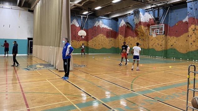 Un entraîneur de basketball, vêtu de bleu et portant le masque, supervise un entraînement dans un gymnase aux murs colorés.