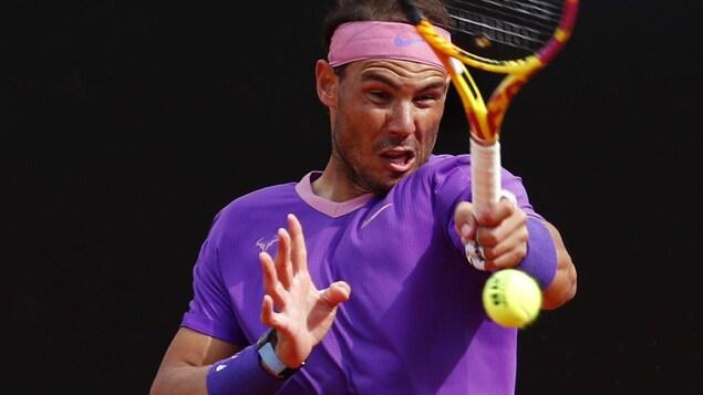 Un joueur de tennis réalise un coup droit de la main gauche.