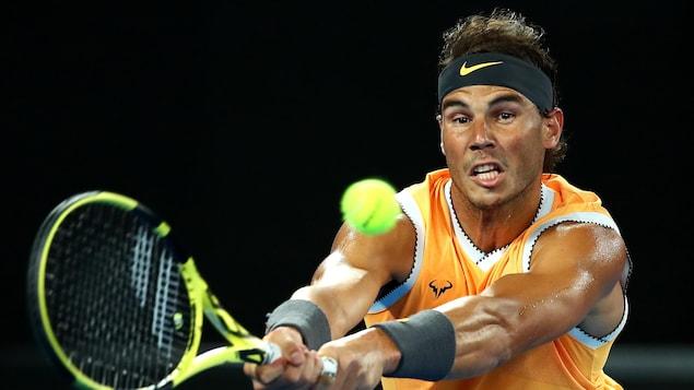 Rafael Nadal renvoie la balle du revers à l'Américain Matthew Ebden dans un match de deuxième tour des Internationaux d'Australie.
