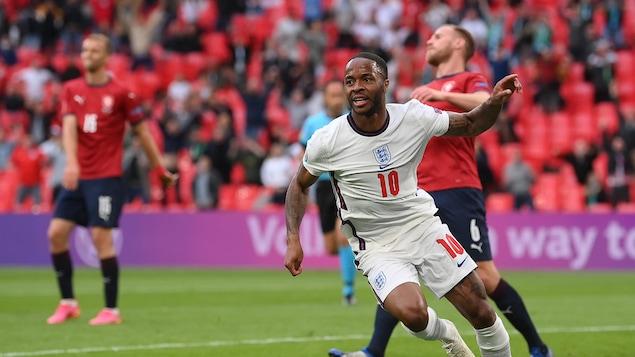 Vêtu de l'uniforme blanc de l'Angleterre, Sterling lève la main et s'apprête à sprinter vers le coin du terrain pour célébrer son but, tandis qu'en arrière-plan, deux joueurs tchèques sont dépités.