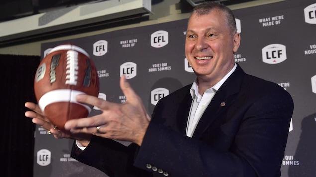 Un homme souriant en complet tient un ballon de football.