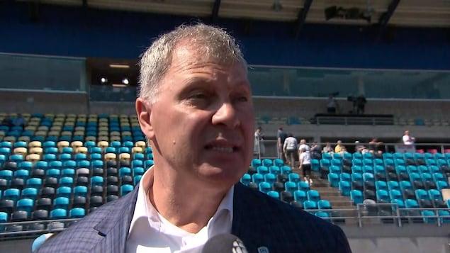 Il répond aux questions des médias avant un match de football à Moncton